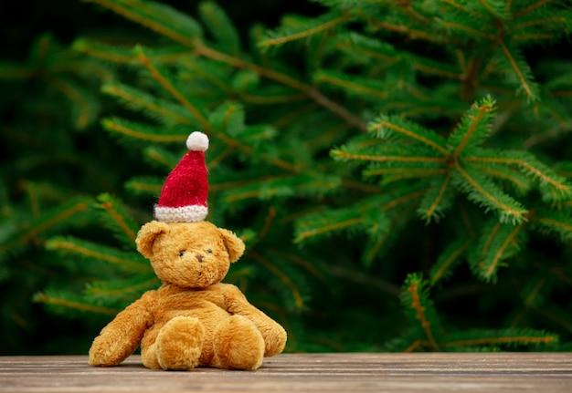 Маленькая игрушка мишка и рождество шляпу на деревянный стол с еловыми ветками на фоне