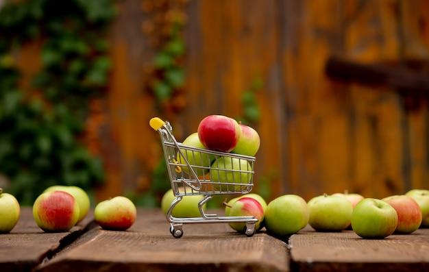 庭の木製の机の上の小さなカートにリンゴ