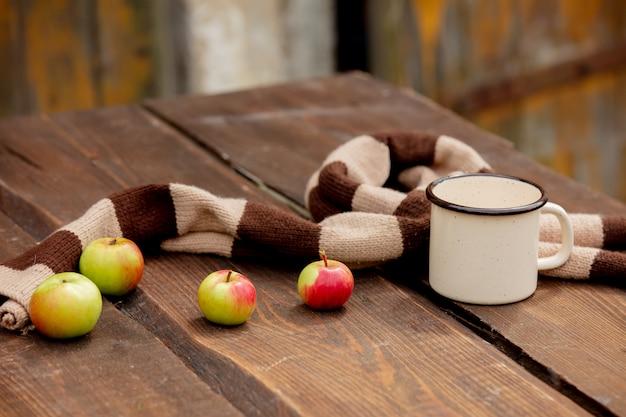 一杯のコーヒーと庭の木製のテーブルの上のリンゴ