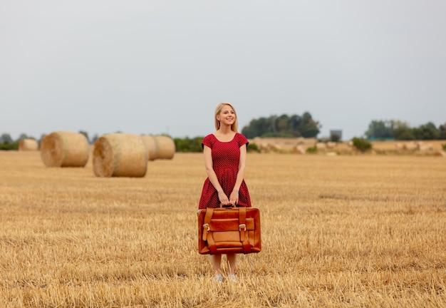 雨の前に麦畑でスーツケースと赤いドレスを着たブロンド