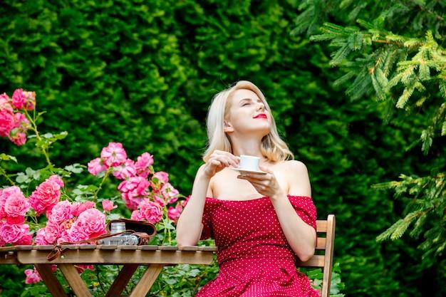 庭でコーヒーを飲みながら赤いドレスで美しいブロンドの女の子