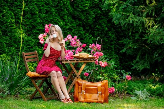 スーツケースと赤いドレスで美しいブロンドの女の子は庭でコーヒーを飲んでいます。