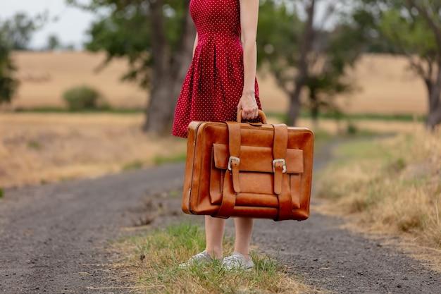 雨の前に田舎道でスーツケースと赤いドレスの女の子