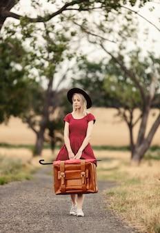 雨の前に田舎道でスーツケースと赤いドレスを着たブロンド