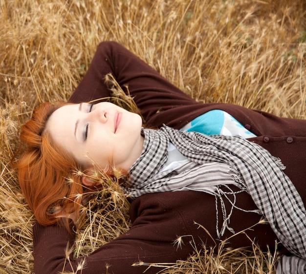 黄色い草の上に横たわって美しい赤毛の女の子。秋のシーズンタイム