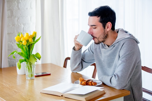Человек сидит за столом с чашкой кофе или чая и ест круассан.