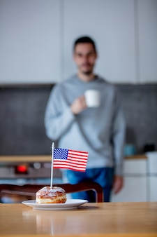木製のテーブルの上の白い皿にアメリカ国旗とドーナツ
