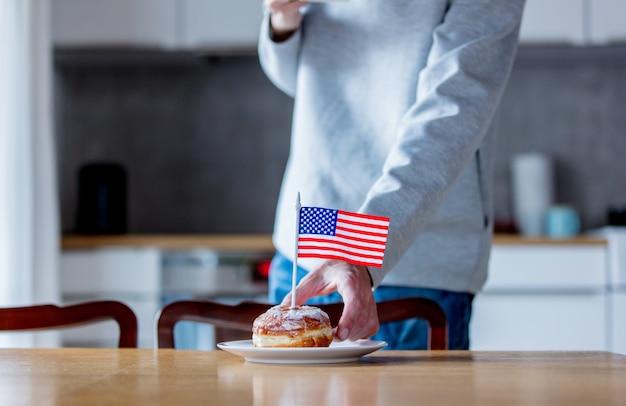 キッチンで木製のテーブルの上の白い皿にアメリカ国旗とドーナツ