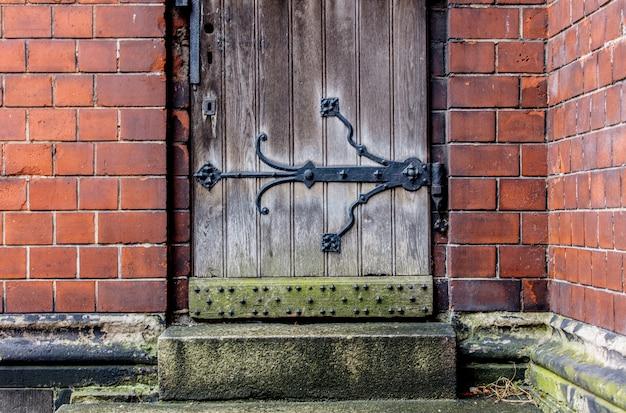 木製のドアと古い大聖堂のレンガの壁