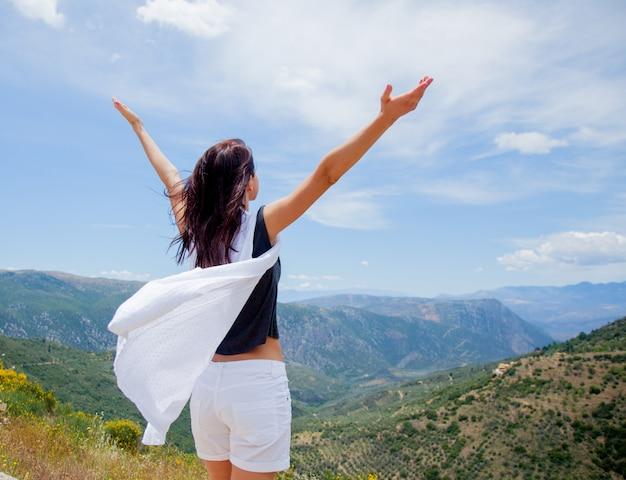 Молодая девушка в белой одежде, стоя на скале в греции