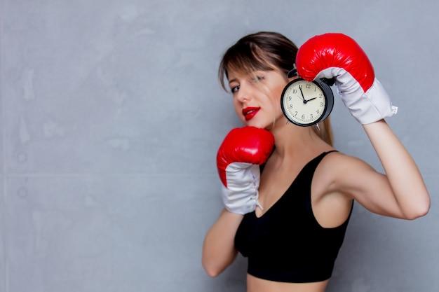 目覚まし時計でボクシンググローブの若い女性