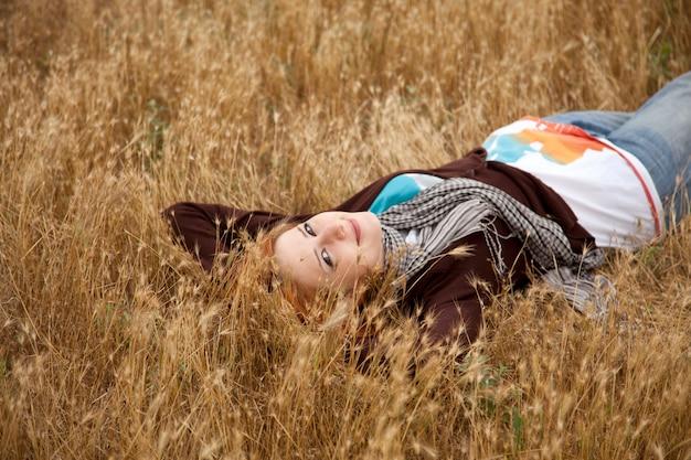 乾いた草の上に横たわる美しい少女。秋のシーズンタイム