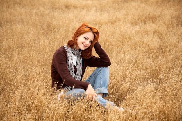 乾いた草の上に立地の美しい少女。秋のシーズンタイム