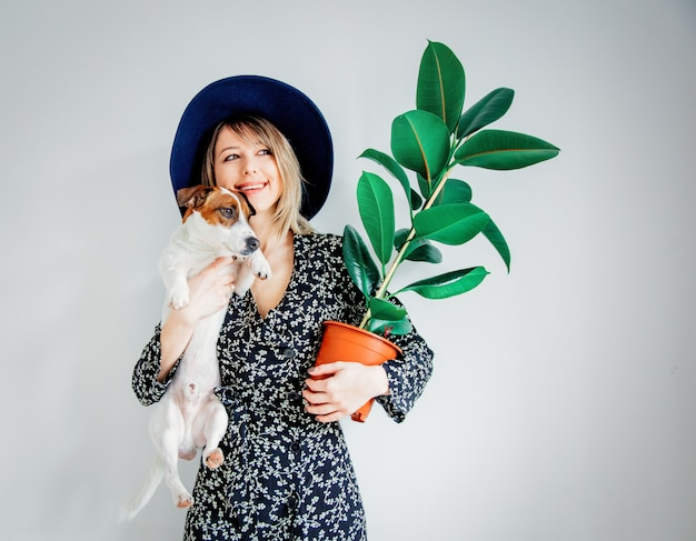 Женщина в модном платье с растением в горшке и собакой
