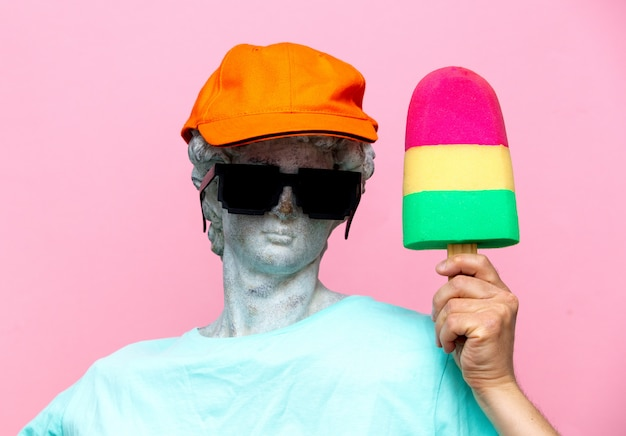 Античный бюст мужчины в шляпе с очками и игрушечным мороженым
