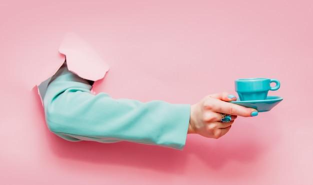 一杯のコーヒーまたは紅茶と古典的な青いジャケットの女性の手