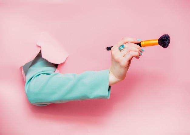 ヴィサージュブラシで古典的な青いジャケットの女性の手