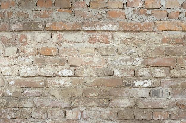 白いペンキの背景を持つ古い赤レンガの壁
