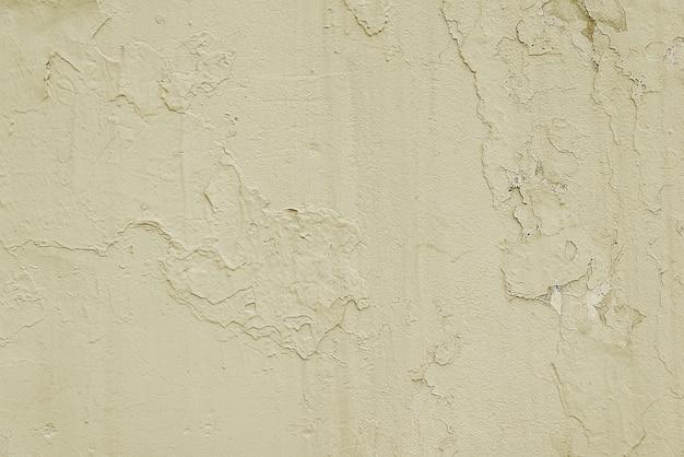古いベージュのひびの入った塗られた壁の背景テクスチャ