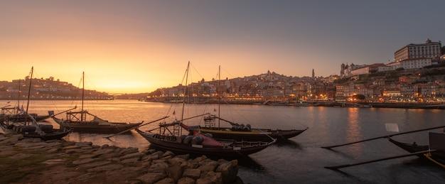 前面の川と日没でポルトの街並みのパノラマと前景と背景、ポルトガルのポルト市のワイン運搬船