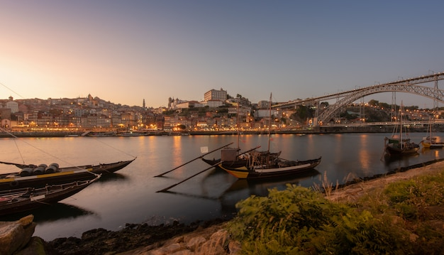 フォアグラウンドでのフロントとワインキャリア船の川と夕日とバックグラウンドでポルトガルのポルトの街で日没のポルトの街並み