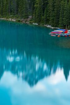 ターコイズブルーの湖とブルースカイ、バンフ、アルバータ州、カナダのモレーン湖の夕日の垂直方向