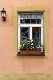 ヨーロッパのオレンジ色のピンクの壁に花と白い窓枠