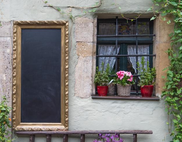 ヨーロッパの古典的な古い壁に塗りつぶす準備ができている黒いチョークボード