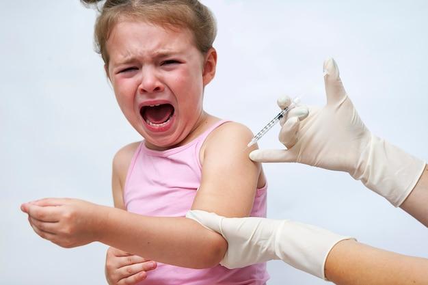 泣いている女の子にワクチン注射を行う医師