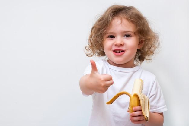黄色のバナナを保持し、親指を現して小さな女の子
