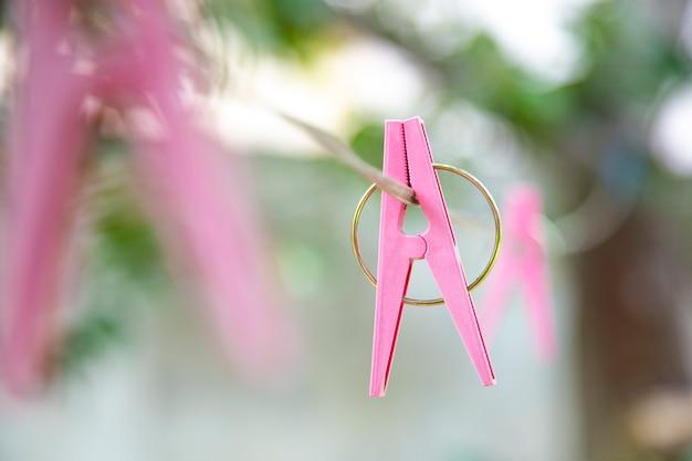 布線にぶら下がっているピンクのプラスチックペグ