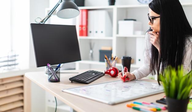 メガネをかけた若い女の子がテーブルのそばに立ち、マーカーを手に持って、磁気ボードに描きます。