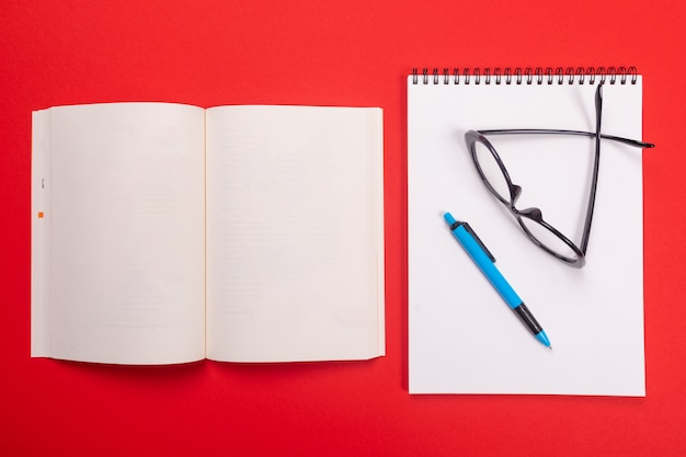 Открыть блокнот и очки с ручкой на белом листе, изолированных на красном фоне