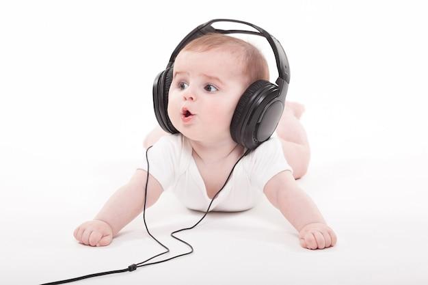 Очаровательная малышка на белом в наушниках слушает музыку