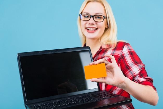 Женщина в очках держит ноутбук и визитку