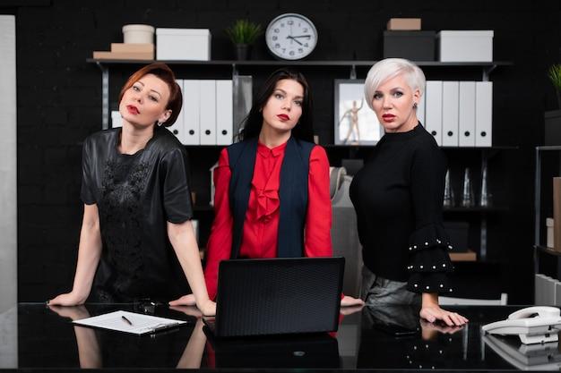 Три деловых женщины стоят возле стола в офисе