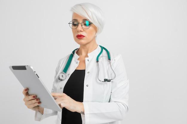 Портрет белокурой женщины в костюме докторов с таблеткой в ее руках изолированных дальше