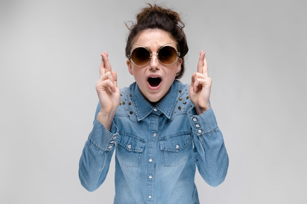 Молодая брюнетка девушка в черных очках. кошачьи очки. волосы собраны в пучок. девушка скрестила пальцы.
