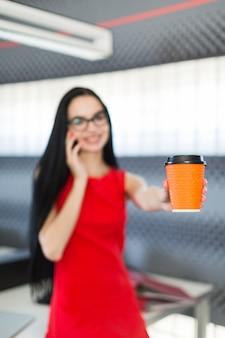 赤いドレスとメガネの美しい若い実業家がオフィスのテーブルの上に座るし、コーヒーカップを保持