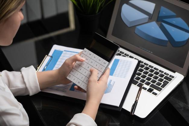 Инвестиционный консультант бизнес-леди анализируя годовой финансовый отчет компании, балансовый отчет работает с калькулятором и ноутбуком