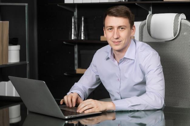 Молодой человек работает на ноутбуке в офисе
