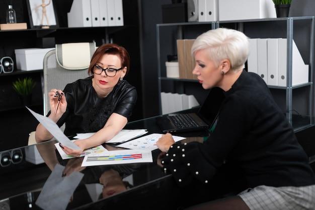 Деловые женщины обсуждают диаграммы на столе в офисе