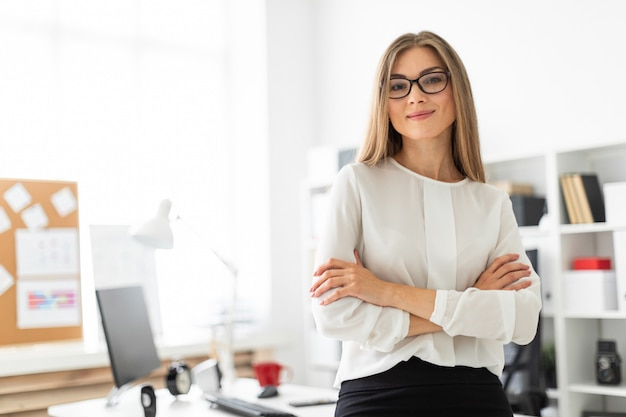 若い女の子がオフィスのテーブルにもたれて立っています。