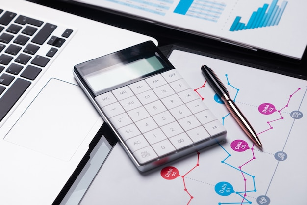 Современный калькулятор на ноутбуке и на листе с графиком