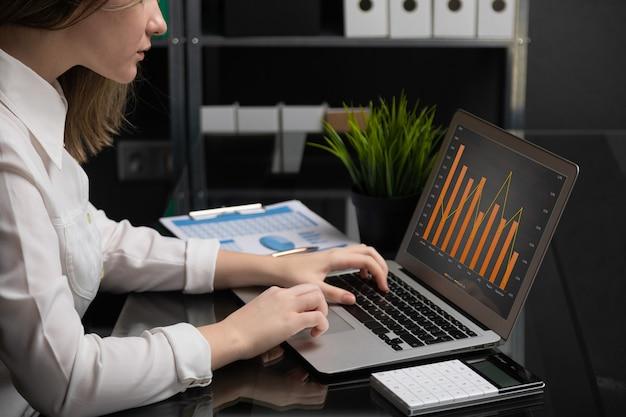 Фрилансер печатает на ноутбуке с пустым чёрным экраном, следующими диаграммами и калькулятором