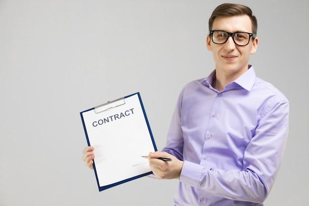 ペンと光に分離された契約のメガネの若い男