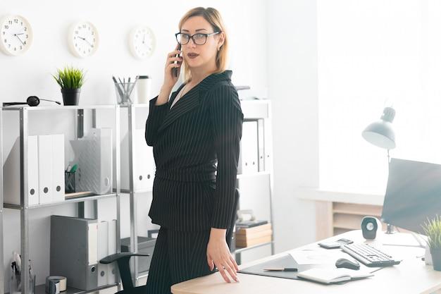 オフィスに立って、電話で話している若い女の子。