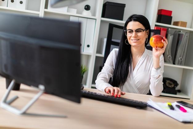 若い女の子がコンピューターの机に座って、彼女の手にリンゴを握り、キーボードに印刷します