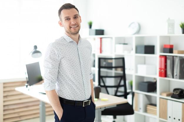 若い男がオフィスのテーブルの近くに立って、両手をポケットに入れている。