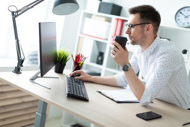 メガネの若い男が事務所のテーブルのそばに立つ